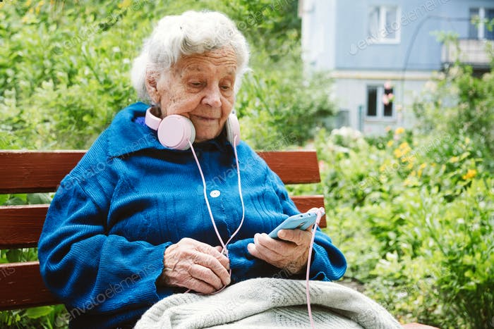 90 year old grandmother with headphones and cell phone sits on a bench on the street