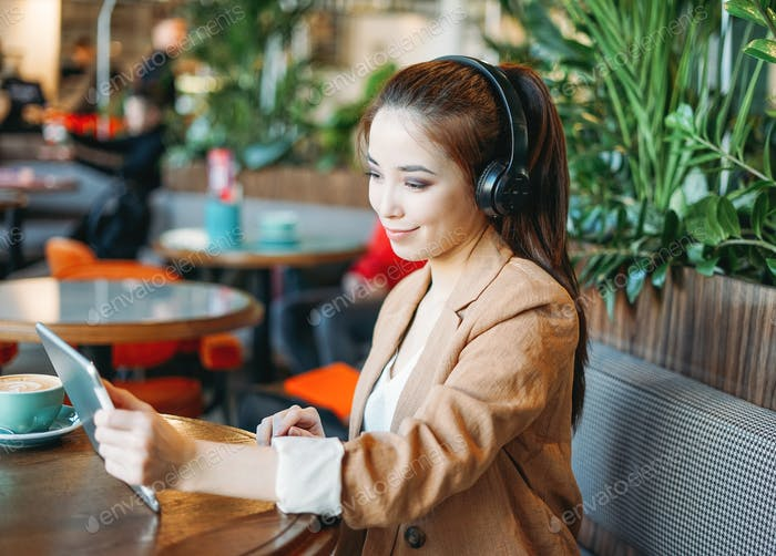 Young smiling asian girl student in headphones communicates by tablet learn foreign language at cafe