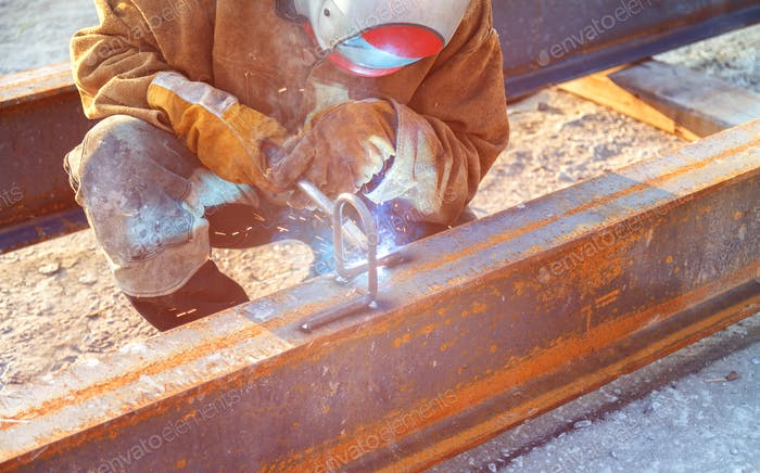 Worker at the enterprise welds a welded metal structure