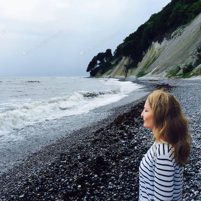 Frau in tiefer Überlegung an einem ruhigen Strand, die den Wellen und der Natur lauscht.