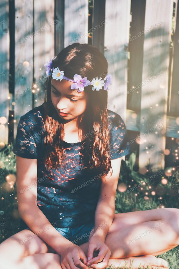 Young girl in a flower crown is sitting on a grass in a summertime dappled with beautiful sunlight