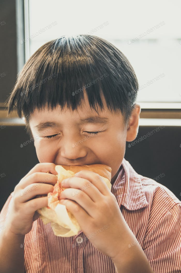 Portrait of a young Asian boy eating yummy burger with oozing facial expression