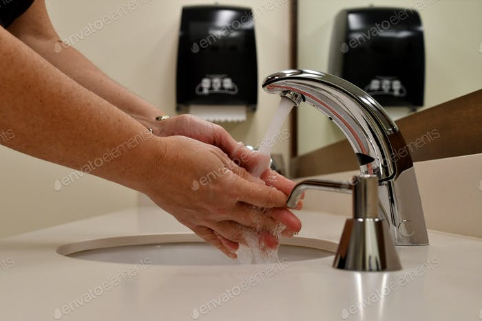 Washing hands in a public restroom, bathroom. Stop the spread of germs, sickness, colds and illness.