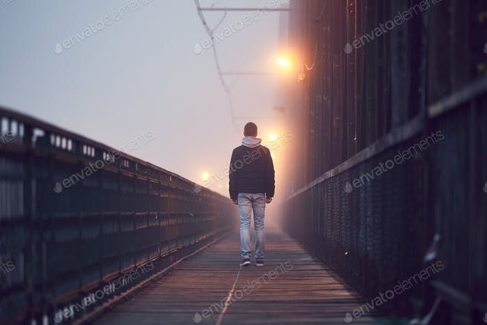 Gloomy weather. Lonely man is walking on the old bridge in mysterious fog.