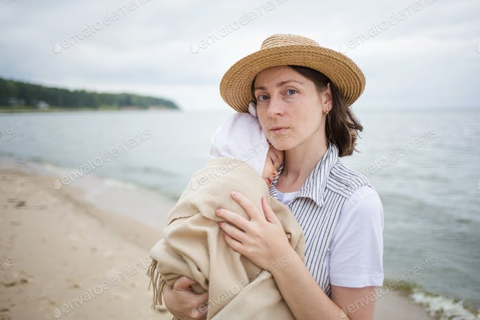 mom holds sleeping baby in her arms. mother and child infant together outdoor see beach