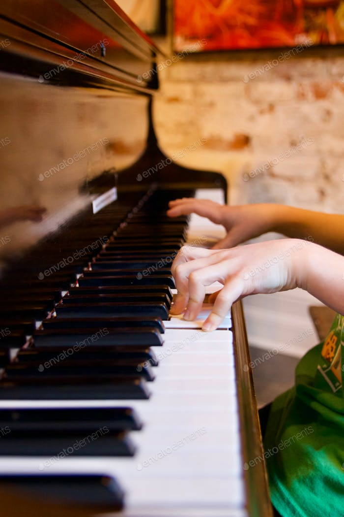 Kids fingers playing a piano