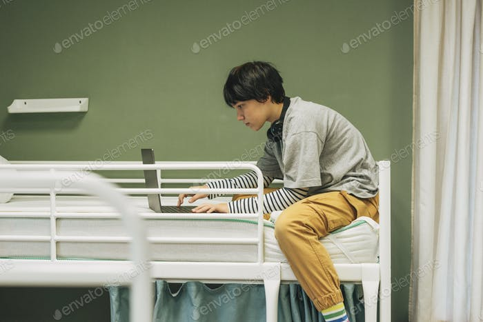 Teen girl with short hair in headphones using laptop on bunk bed at the hostel