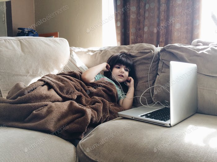Little girl using earbuds with the computer.