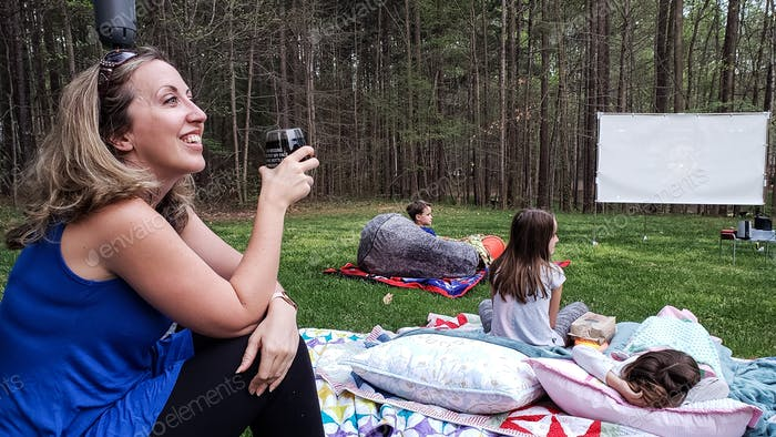 Resourceful millennial having a backyard wine and movie party with the neighbors with social