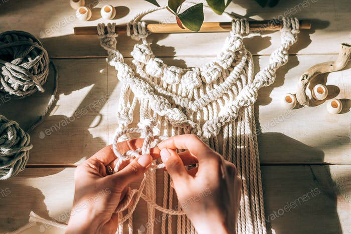 Close up of women's hands weaving macrame in a home workshop,top view.Handmade concept.Home decor.