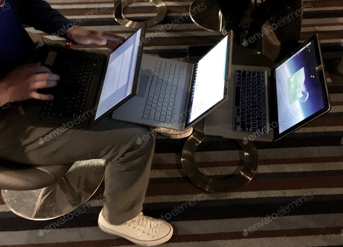 Overhead shot of a man using three laptops stacked in a row