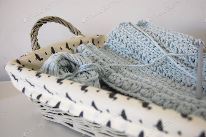 A grey basket of pale blue crochet with a ball of chunky yarn