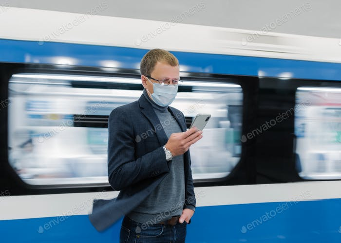 Man in eyewear and protective medical mask, uses modern phone, travels by public transport