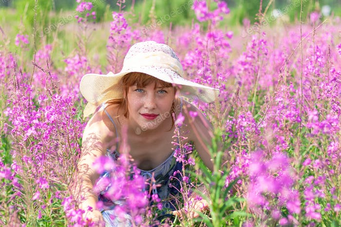 A young girl in a straw hat in a field with lilac flowers on a sunny summer day. Scenery.