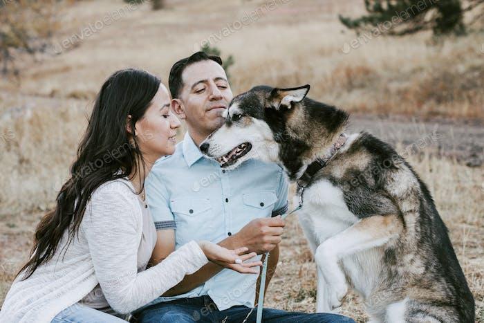 A young Hispanic couple play with their husky