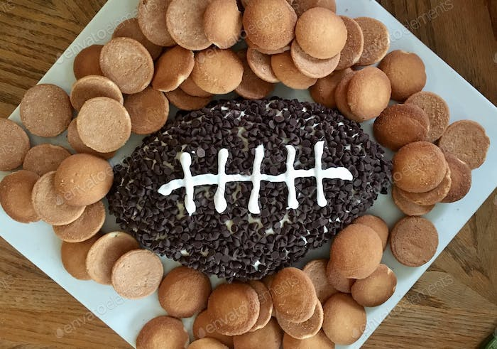 Sweet dip in shape of football with wafers for super bowl party