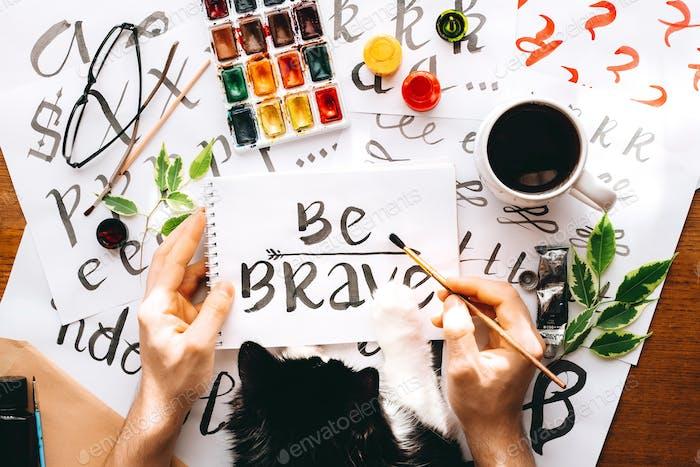 Sei mutig Draufsicht Mann und Katze schreiben auf Papier Blatt Leinwand Kalligraphie Wort Sei mutige Zeichnung