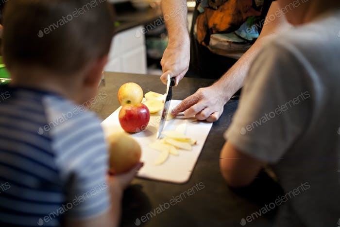 dad cutting apples on a cutting board