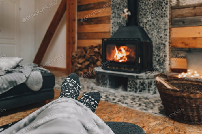 Selective focus shot of woman legs in Christmas socks with a fireplace in the background.