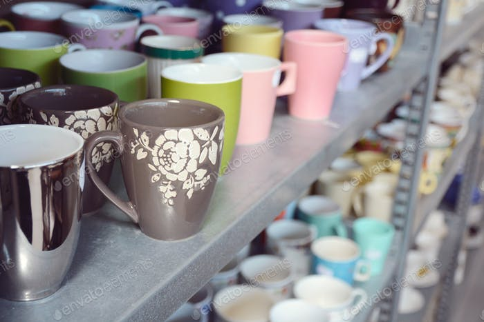 Second-hand mugs in metal storage rack for sale