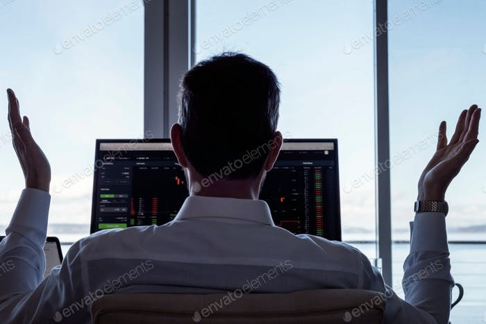Hands up businessman at desk with computers