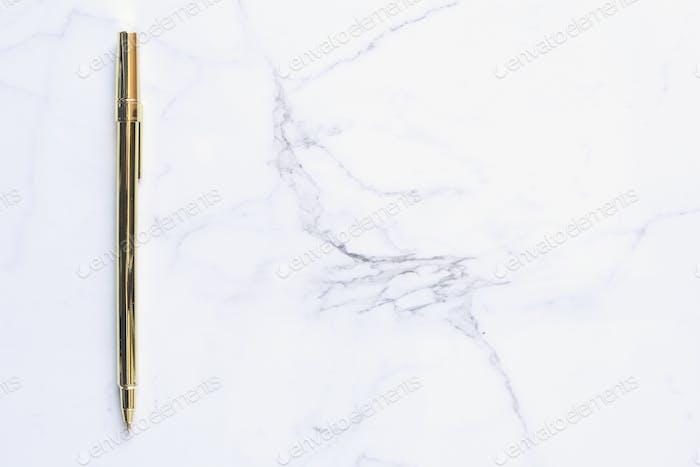 Bolígrafo dorado sobre mármol