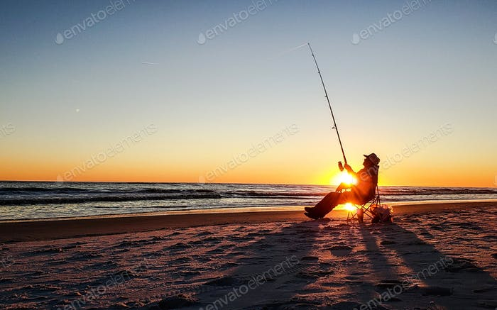 Active senior surf fishing at the beach during golden hour as the sun goes down...