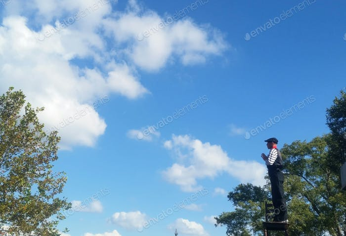 Outdoor entertainment in Disneyland  with beautiful sky showing clouds and entertainer on ladder.