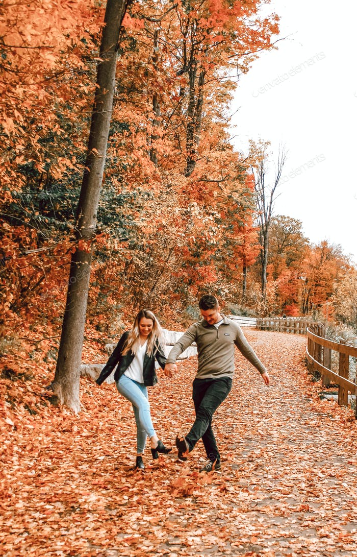 Couple kicking leaves in Fall