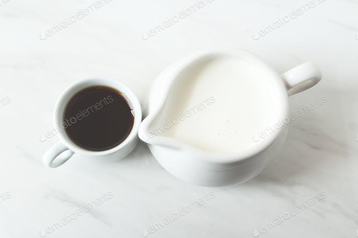 Black cup of espresso and creamer