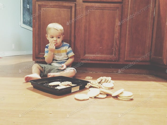 Toddler eating a whole tray of cookies he knocked on the floor