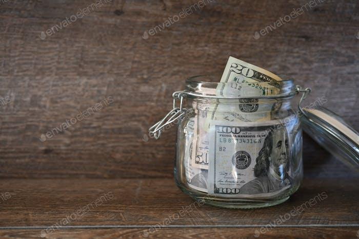 Dólares, dinero, caja de dinero en moneda, billetes de cien dólares, salario, ingresos adicionales, ajetreo lateral, ganancias