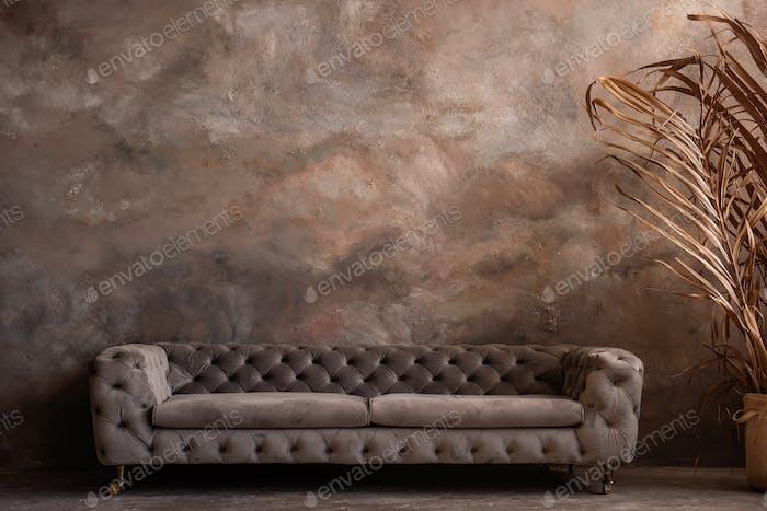 Dark loft interior with trendy, stylish gray sofa, dry grass by the window. Concrete background