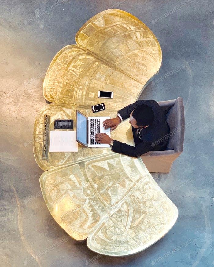 Man posting on several social media on his work desk.
