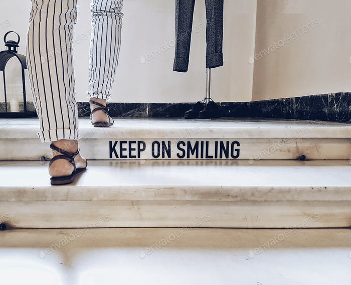 Keep on smiling quote on a staircase printed. Footsteps up.