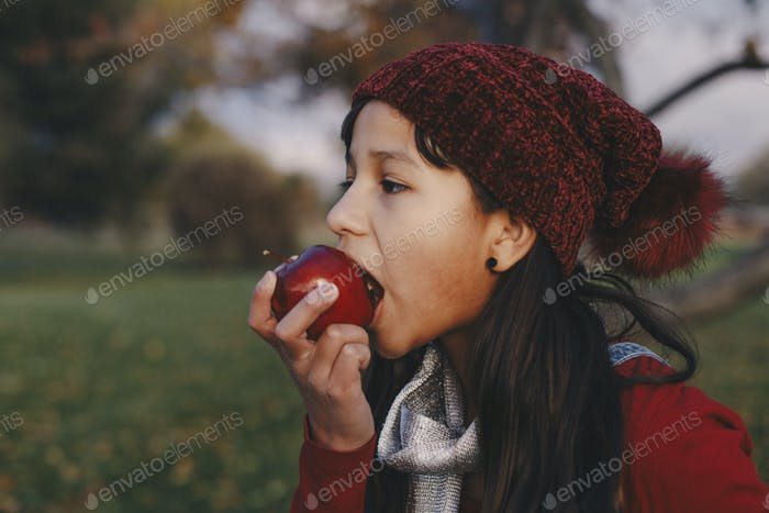 A young girl taking a bite of an apple