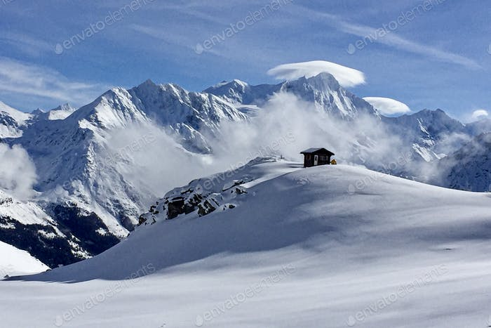 snow-capped mountains, blue sky and a small house in the mountains. Light and airy pic.