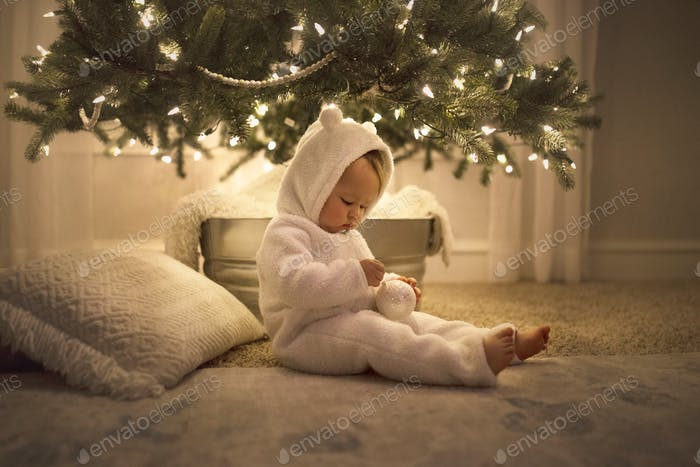 A bundled up toddler filled with wonder beneath the brightly lit Christmas tree.
