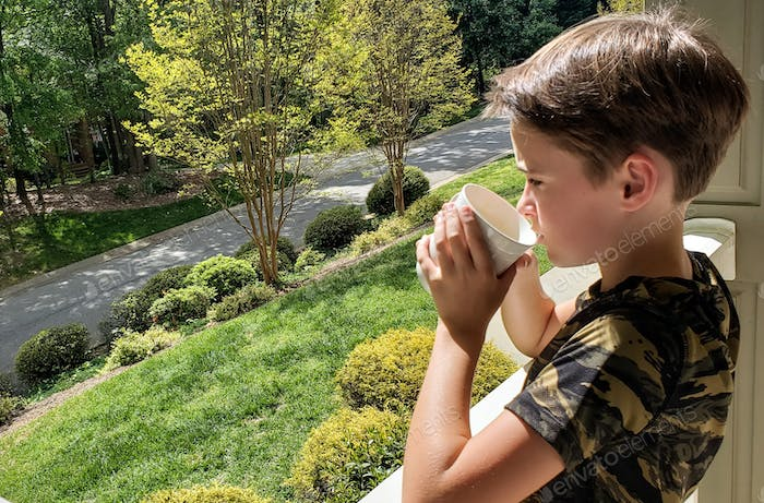 Little boy homebound by coronavirus sipping his hot coffee in the morning wishing to be outside in