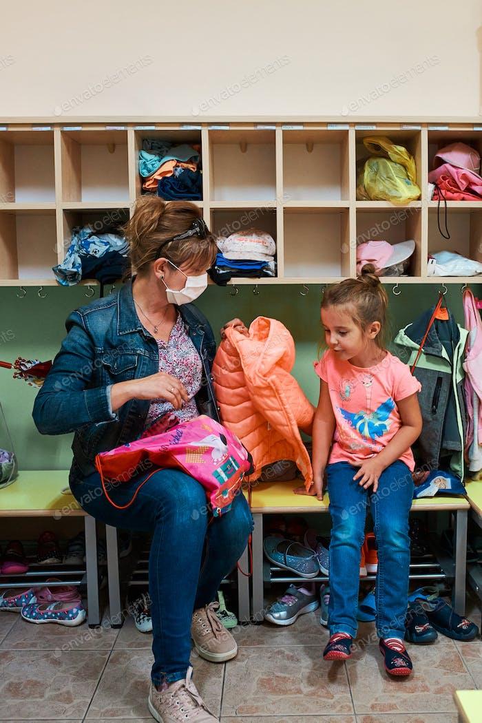 Kind kleines Mädchen, das sich in der Umkleidekabine im Kindergarten mit Mütterhilfe umzieht