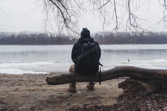 man with hiking gear on stopped looking at frozen lake