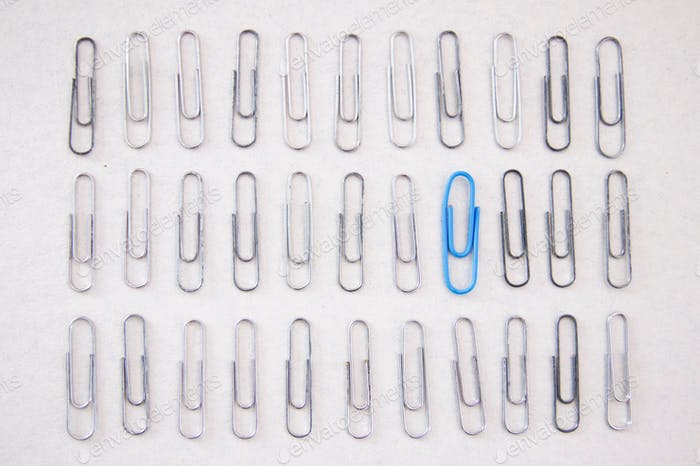 Blue paper clip among silver paper clips