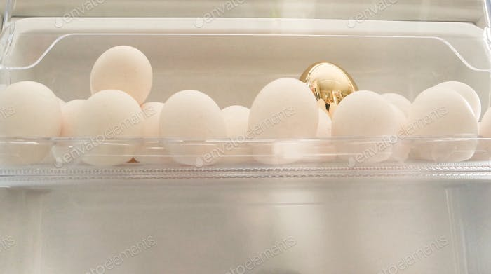 One golden egg between all white eggs in the refrigerator.