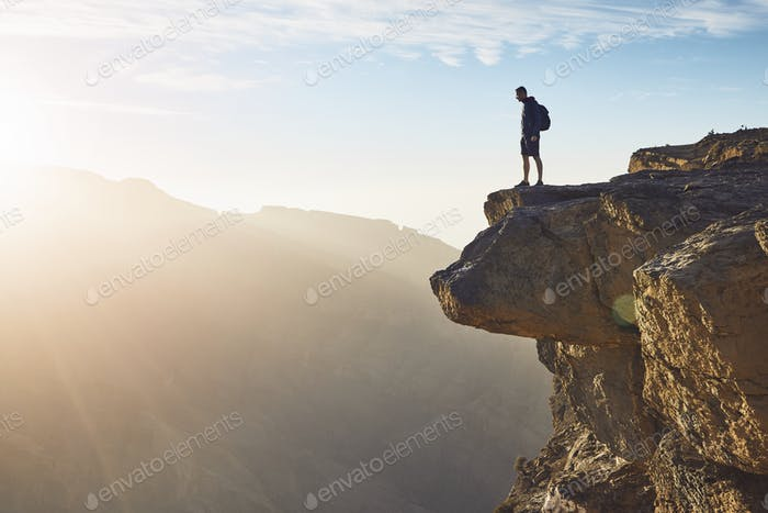 Young tourist with backpack standing on the edge of cliff at sunrise