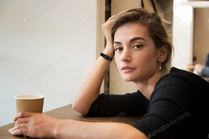 Young woman in cafe sitting alone, bored, drinking coffee