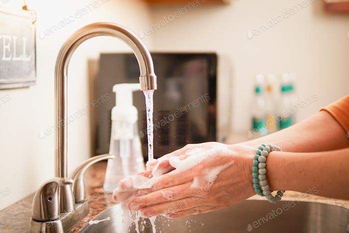 Frau Waschen Hände in der Spüle mit heißem Seifenwasser verhindern Krankheit persönliche Hygiene