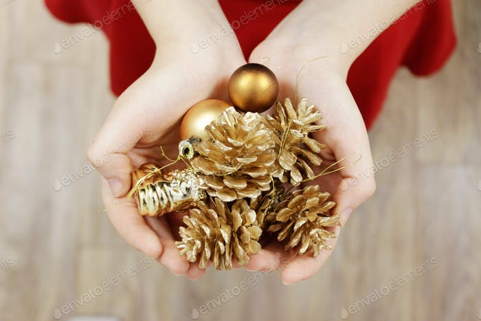 Woman's hands holding golden tree ornaments