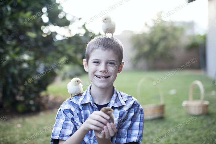Boy with chick on head and shoulders.