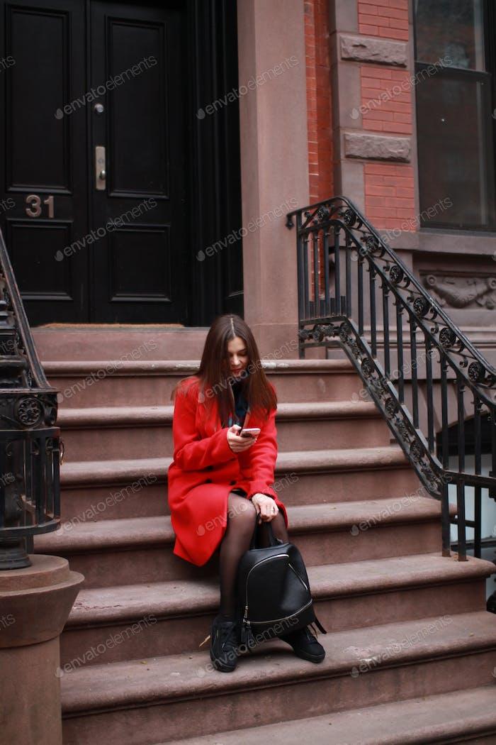 hermosa mujer caucásica con un abrigo rojo en la ciudad en la calle, sentada en los escalones de la casa