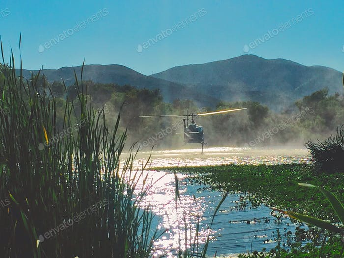 Emergency helicopter utilizing water from a lake to fight fires.